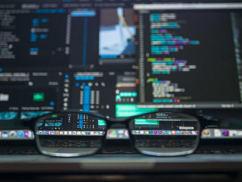 código escrito em computador ao fundo com óculos em destaque