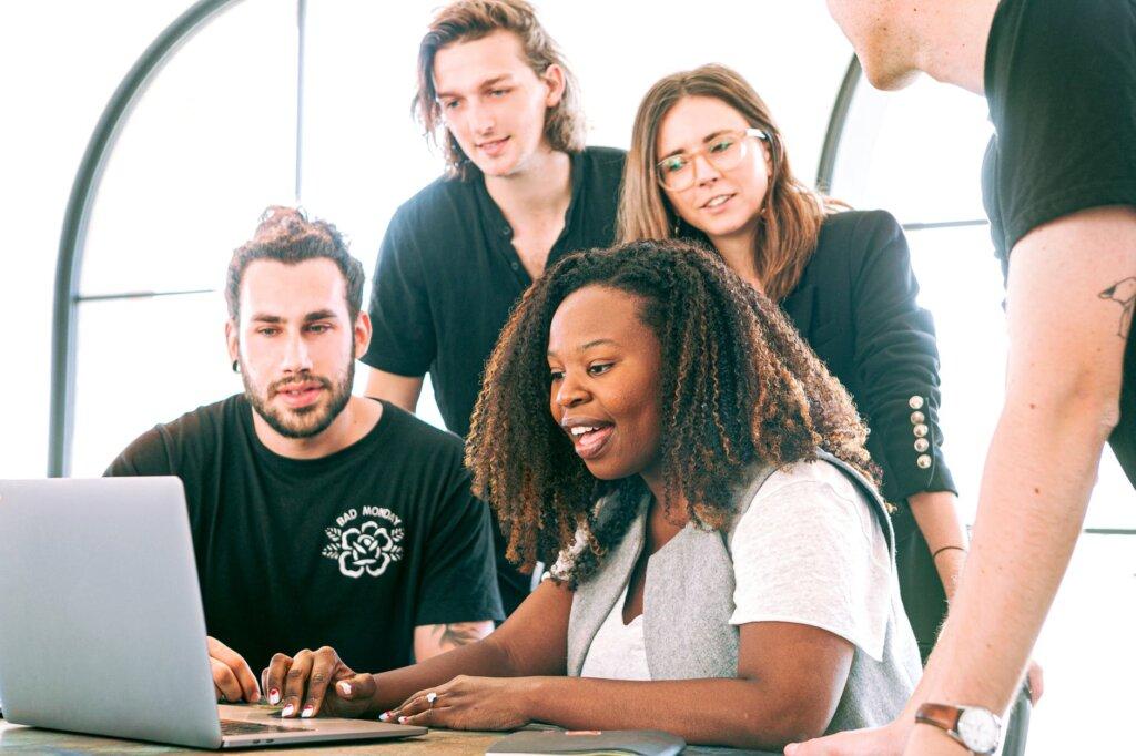 equipe de trabalho reunida em frente a um notebook